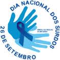 Logotipo do Dia Nacional do Surdo. Desenho de duas silhuetas de mãos espalmadas azuis com uma fita azul formando um laço sobre elas. Frase: Dia Nacional do Surdo 26 de setembro.