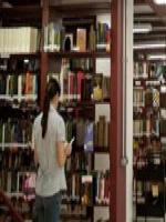 Imagem de uma estante de livros com uma figura feminina na frente.