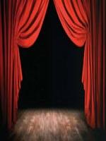 Cortinas vermelhas de teatro, sobre um tablado de madeira marrom. O fundo é preto.