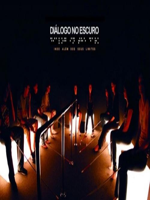 Fotografia de um grupo de pessoas em sala escura, sentadas em bancos com bengalas longas.  Na parte superior da imagem título da exposição em letras brancas e braile.