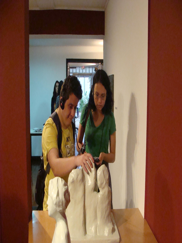 Dois jovens com fones e aparelhos de audioguia tocando escultura de Lasar Segall na exposição Esculturas Táteis do Museu Lasar Segall