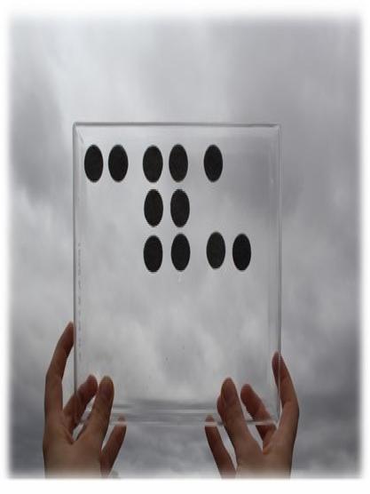 """Duas mãos seguram uma placa retangular de acrílico transparente com a palavra """"céu"""" em braile feita com feltro adesivo. A placa está posicionada para o céu encoberto por nuvens em tons de cinza, que aparece através da transparência do acrílico"""