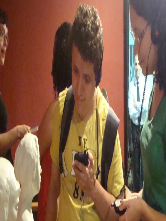 Um rapaz com com deficiência visual e uma moça sem deficiência utilizam aparelhos de audioguia com audiodescrição na exposição tátil do Museu Lasar Segall. Atrás deles há duas mulheres.